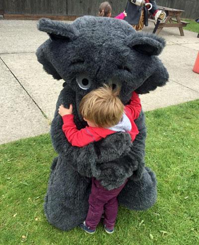 Furry mascot cuddling the kids