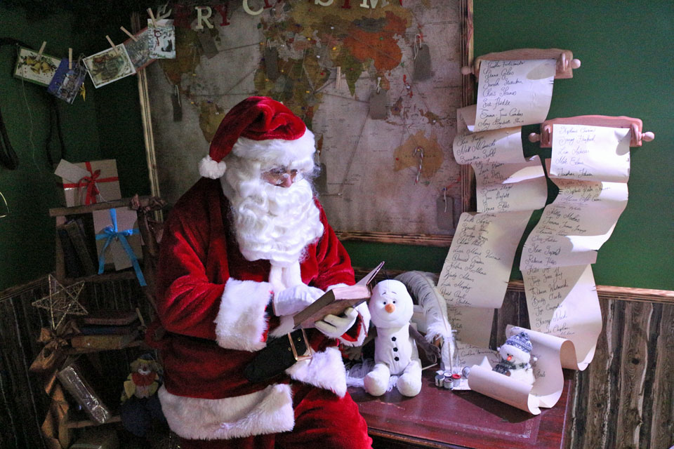 Santa reading the naughty list in office